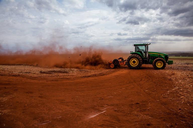 Trator passa máquina em terra e levanta poeira vermelha