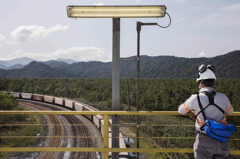 Homem com capacete, de costas, olha para trem passando sob ponte