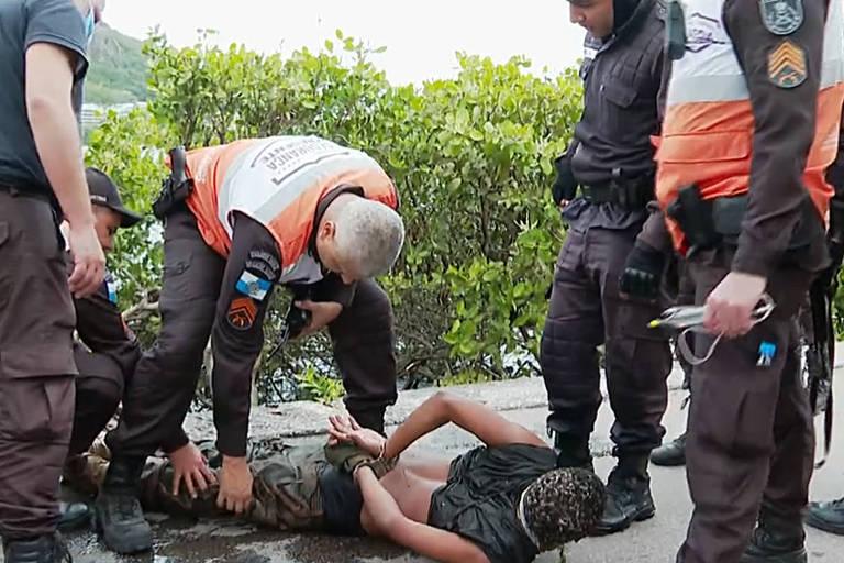 Um homem está deitado de bruços no chão sendo algemado por policiais que estão de pé em volta dele