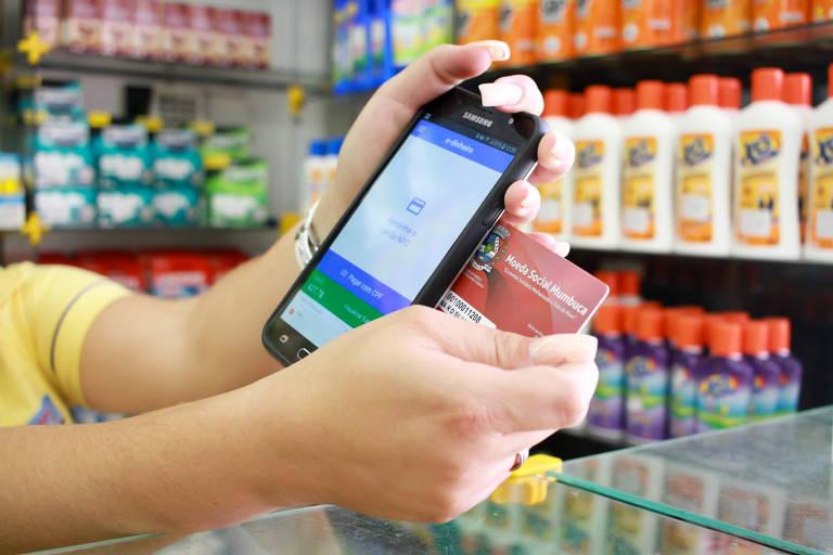 Pessoas usando cartão e telefone celular para pagar compra no comércio de Maricá