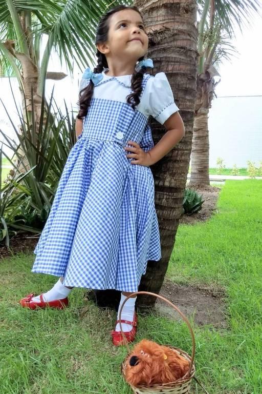 Criança branca usa vestido xadrez azul e branco e os sapatos vermelhos do filme. Ela está em pé na frente de uma árvore