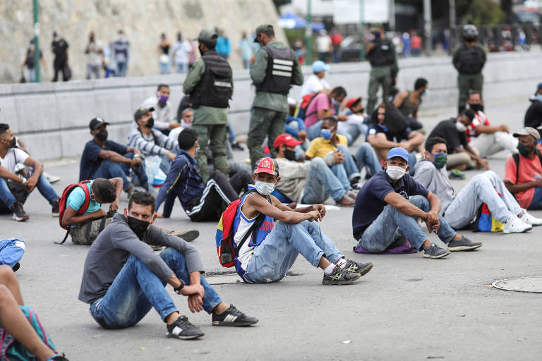 Pessoas de máscara sentam no chão enquanto policiais estão em pé