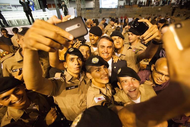 Então deputado federal, Jair Bolsonaro participa em 2017 de formatura de soldados da Policia Militar de Minas Gerais, em Belo Horizonte; foto mostra aglomeração de soldados em torno do deputado, e um deles segura no alto um celular para fazer uma selfie do grupo