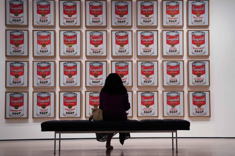 Mulher olhando quadro com várias imagens repetidas de latas vermelha e branca
