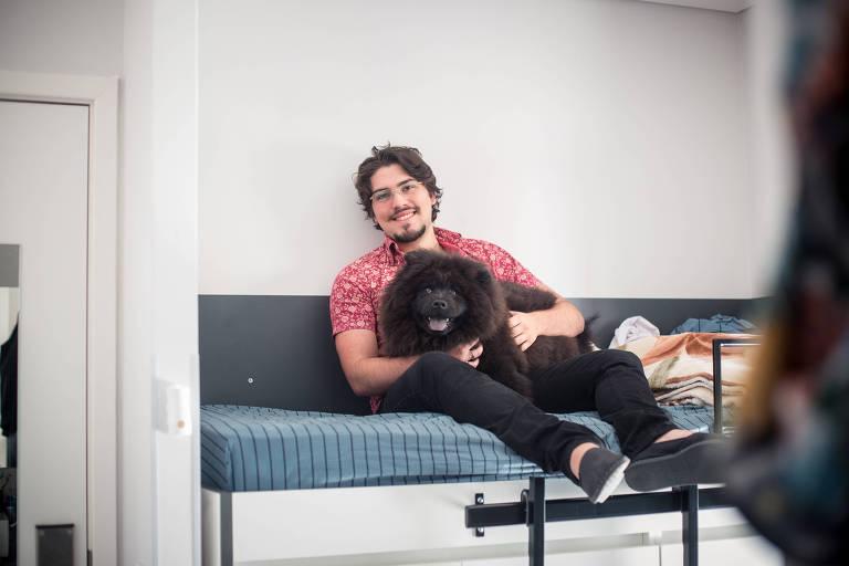 Homem sentado em cama com cachorro preto no colo, sorrindo