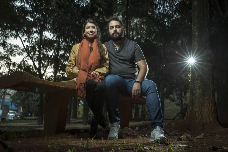 Homem e mulher sentados em banco de madeira, em praça, sorrindo