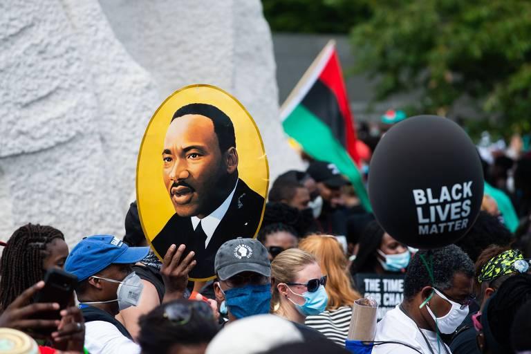 Manifestante exibe imagem do ativista Martin Luther King durante marcha  em Washington contra o racismo e a violência policial