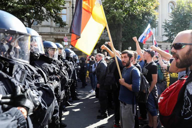 Linha de policiais com escudos e capacetes com proteção facial de frente para linha de manifestantes sem máscara e com bandeiras