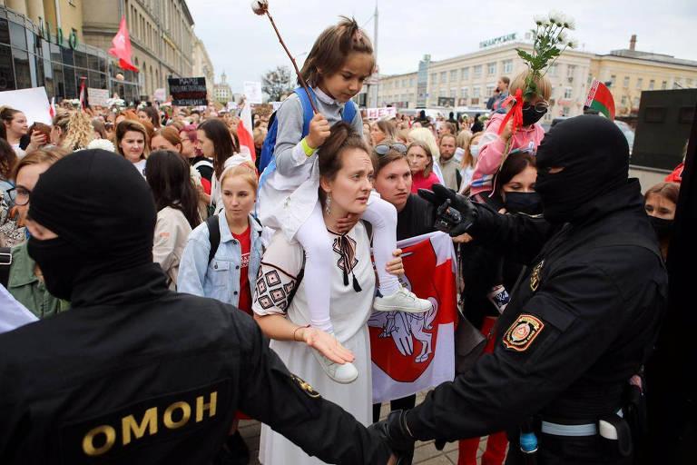 Mulheres, uma delas com uma criança nos ombros, em frente a corrente de policiais de preto