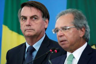 FILE PHOTO: Brazil's President Jair Bolsonaro listens Brazil's Economy Minister Paulo Guedes during a media statement announcing economic measures, amid coronavirus disease (COVID-19) outbreak, in Brasilia