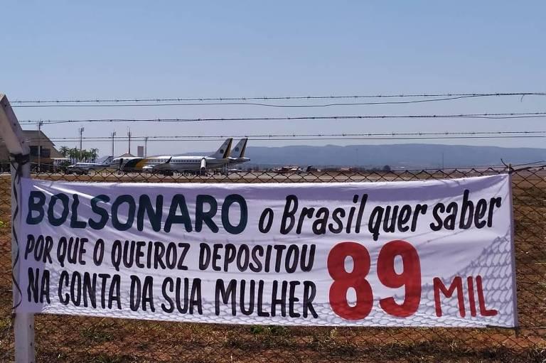 """Faixa confeccionada por manifestantes em Caldas Novas, interior de Goiás, que apresenta a frase: """"Bolsonaro, o Brasil quer saber: Por que o Queiroz depositou R$ 89 mil na conta da sua mulher?"""""""
