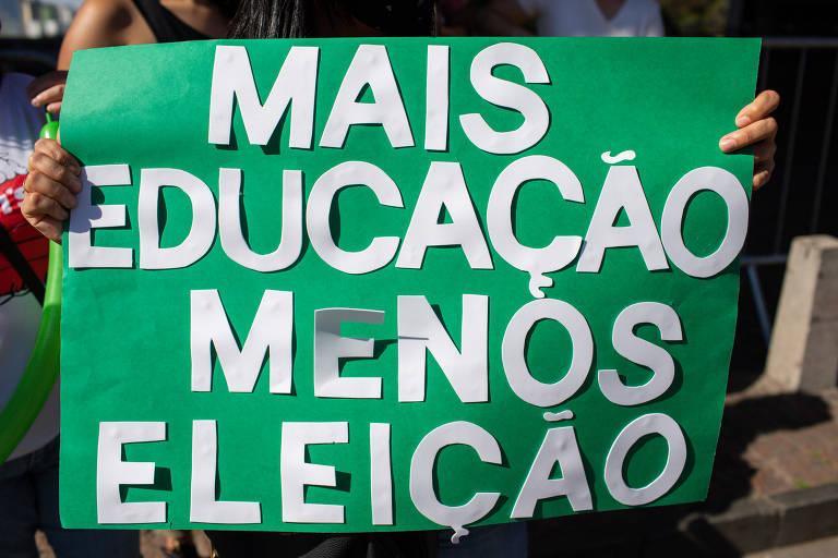 """Sindicato de escolas do estado chegou a entrar com mandado de segurança contra o prefeito Bruno Covas, mas Justiça negou pedido de liminar para reabrir estabelecimentos a partir de 8 de setembro; na foto vemos um cartaz verde que cobre quem o está segurando e traz, em letras brancas, os dizeres """"Mais educação menos eleição"""""""