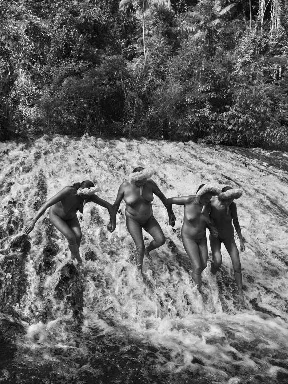 Quatro mulheres Zo'é andam sobre uma das corredeiras, comuns no ambiente de relevo alto típica da região em que vivem os índios, próxima das Guianas. São elas, da esquerda para a direita: Tatytúsíng, Bohé, Tatytú e Jurusí