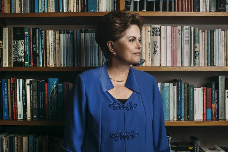 A ex-presidente Dilma Rousseff em entrevista em seu apartamento, em Porto Alegre (RS); Dilma posa em frente a uma estante de livros, com o rosto virado para a esquerda; ela usa uma blusa azul e um colar fino, está bem penteado, com cabelos curtos, e maquiada