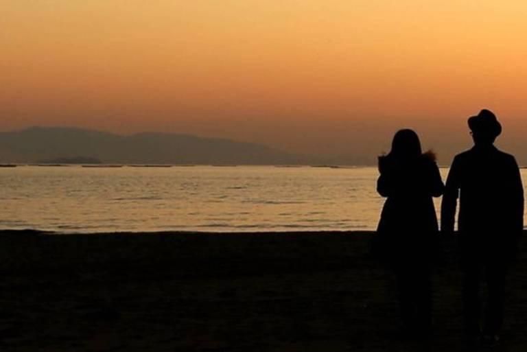 Dois casais olham para o pôr do sol durante o primeiro dia de primavera na praia de Shinmaiko em Tatsuno, província de Hyogo, Japão