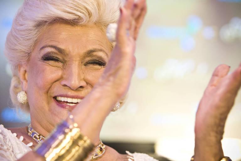 hebe de cabelos loiros platinados sorri e aplaude com as duas mãos