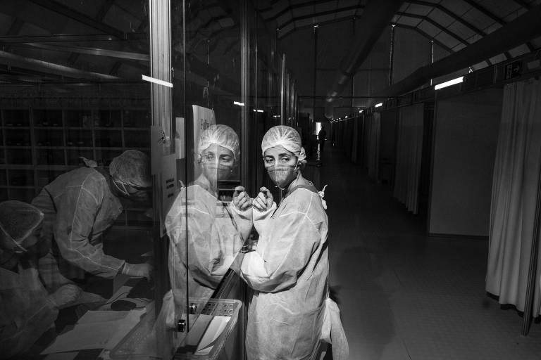 uma foto preto e branco mostra uma enfermeira de máscara no corredor de um hospital