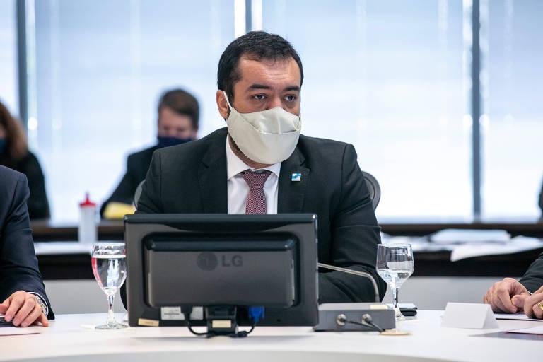 O governador interino, Cláudio Castro, durante reunião com o secretariado; ele está de terno, gravata e máscara, diante de uma tela colocada sobre uma mesa de reunião