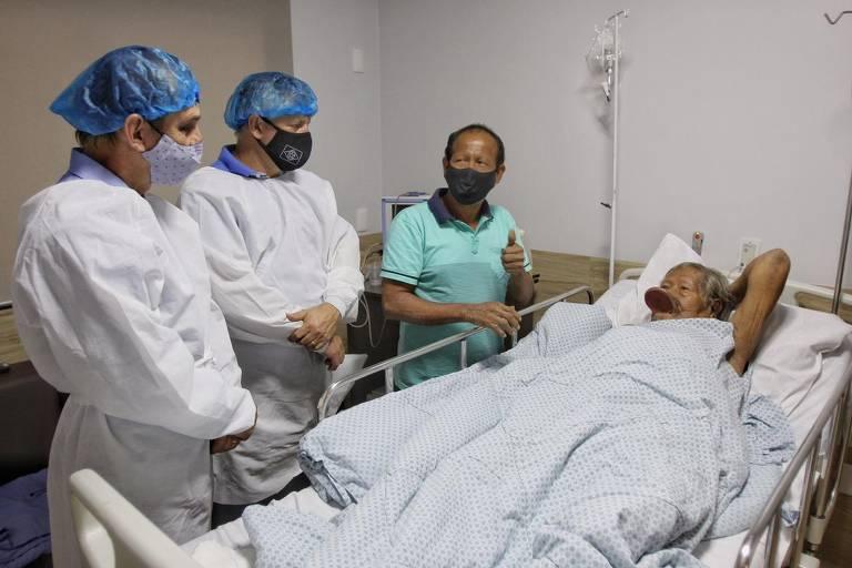 Raoni recebe representantes do governo do MT no hospital Dois Pinheiros, em Sinop; na ocasião, foram detectadas duas úlceras gástricas, inflamação no cólon e uma infecção intestinal; o cacique está num leito, e à esquerda há três pessoas que o visitam