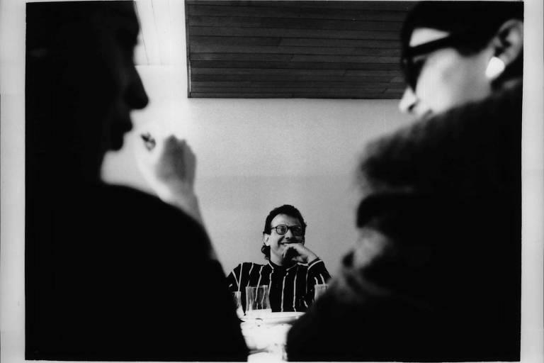 retrato em preto e branco de homem sentando à mesa, com a mão no queixo, rindo. de frente a ele, duas jornalistas também riem