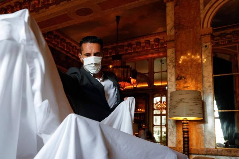 Um funcionário remove panos que cobriam móveis nos preparativos para a reabertura do hotel Crillon, em Paris