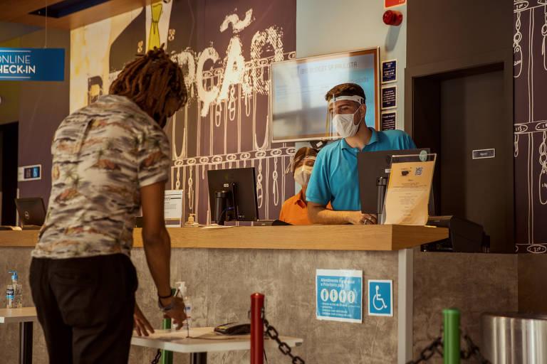 Homem com máscara e face shield, atrás de balcão, olha para outro homem de máscara que escreve em papel