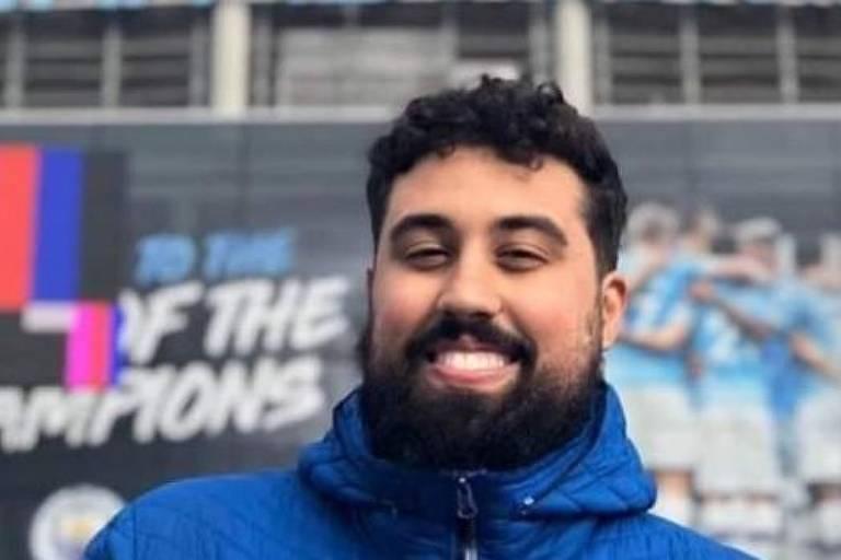 Rosto de um moço de barba preta, sorrindo