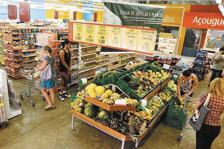 Mercado na zona Sul de São Paulo, onde há bancadas com frutas e preços, gôndolas com produtos e uma placa em laranja indicando o açougue do mercado