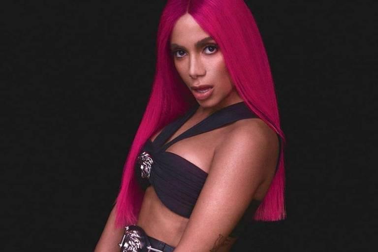 Anitta está de cabelo longo rosa, com calça justa preta e um topo preto