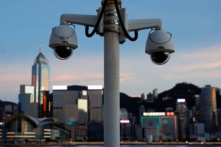 Duas câmeras no primeiro plano com os prédios de Hong Kong desfocados ao fundo