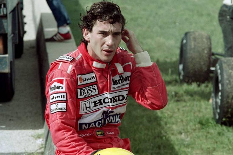 Senna sentado numa mureta com macacão vermelho e capacete amarelo à frente