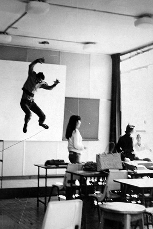 numa sala de aula, um aluno salta enquanto outra olha para o outro lado