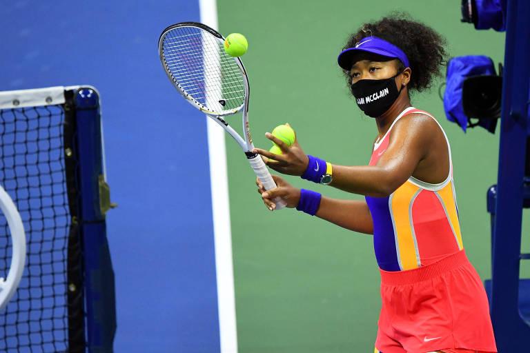 Osaka, de máscara, se prepara para rebater uma bola em direção às arquibancadas