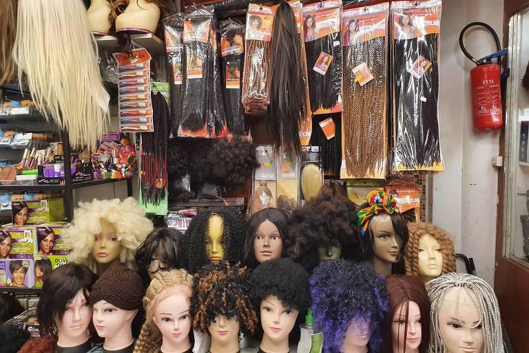 apliques de cabelo pendurados no teto e cabeças de manequim com perucas de cabelo crespo de várias cores