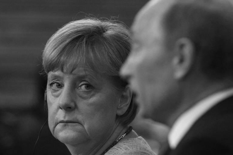 A chanceler alemã, Angela Merkel, observa o presidente russo, Vladimir Putin, durante coletiva de imprensa em 2013