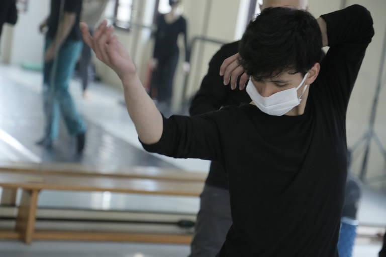 Na foto, homem com máscara faz passo de balé