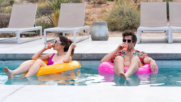 casal flutua em boias coloridas na piscina