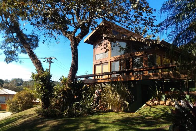 Casa com grande gramado na frente, com árvores