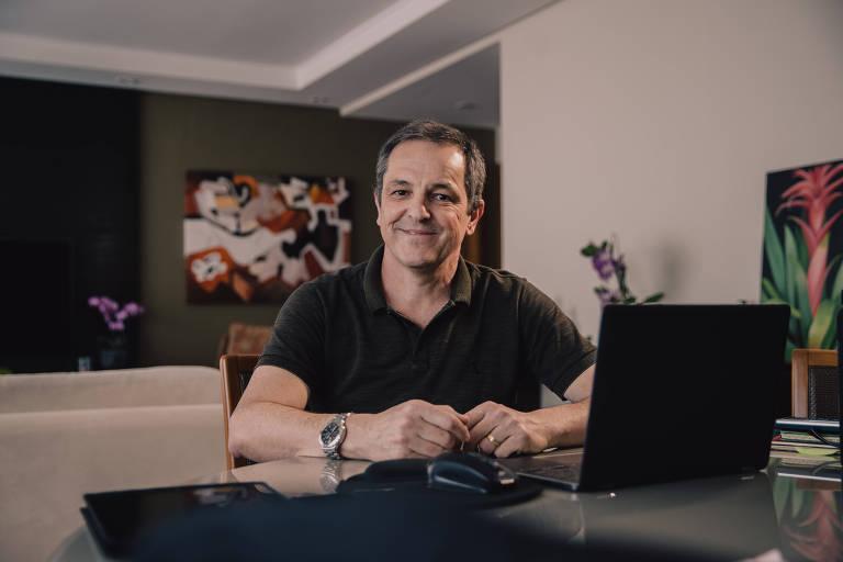 Homem de camiseta preta sentado em mesa em sala, com notebook, sorrindo