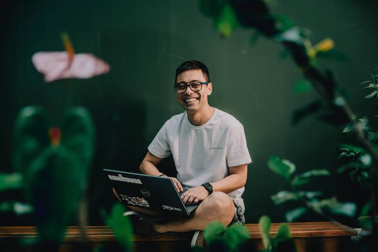 Homem sentado em banco de madeira, com notebook no colo, sorrindo