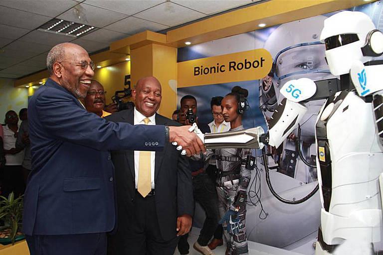 Sorrindo, o primeiro-ministro de Uganda aperta a mão de um robô