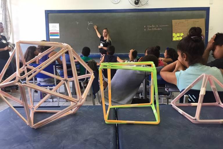 O projeto, que usa abordagem desenvolvida em Stanford, foi aplicado a crianças de duas escolas de Cotia, na região metropolitana de São Paulo; vemos uma sala de aula, ao fundo a professora na lousa e, em primeiro plano, formas geométricas tridimensionais feitas com canudinhos