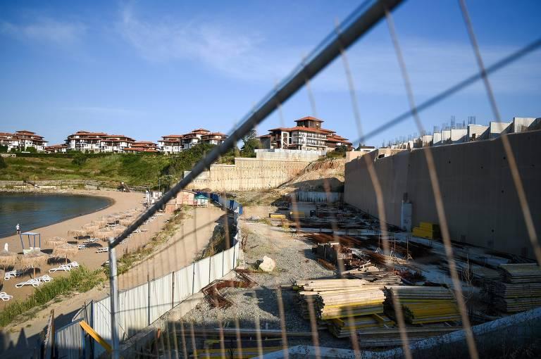 Grade em primeiro plano e muro de construção, com praia ao fundo