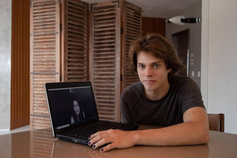 Dan Esteve Lannes, 21, ao lado do computador que mostra a foto da mãe, Hilana