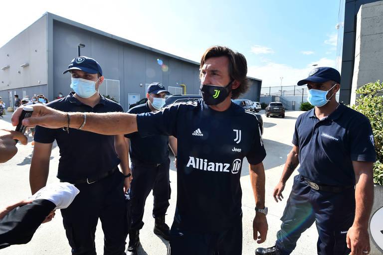 Homem com camiseta esportiva e máscara preta acena para pessoas