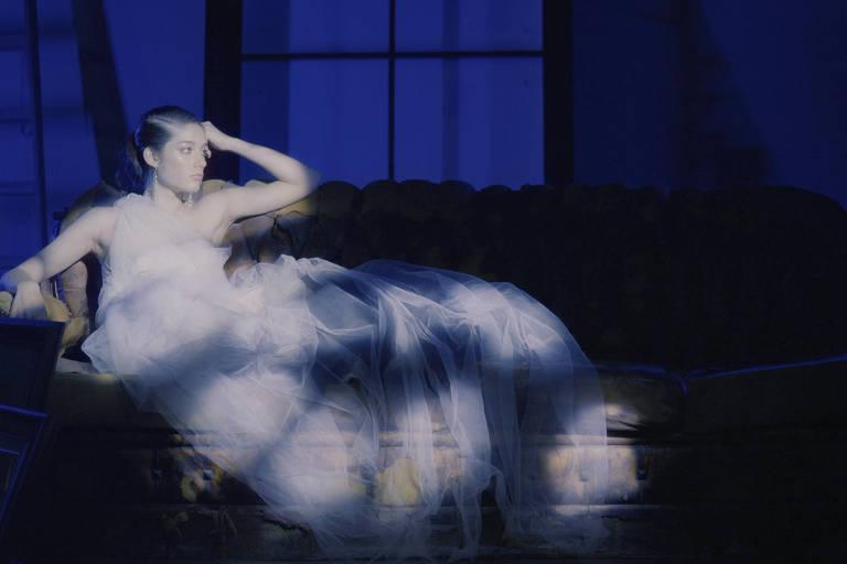 mulher de vestido leve branco sobre poltrona