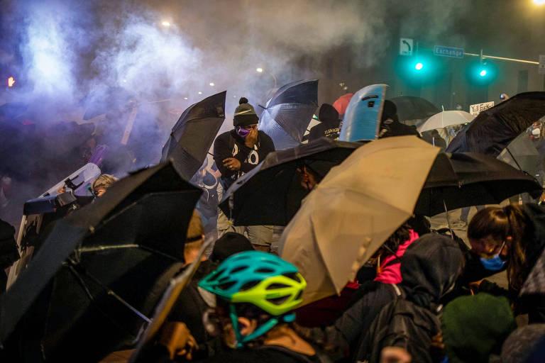 Em cena caótica, pessoas se cobrem com guarda chuvas enquanto tentam escapar de gás