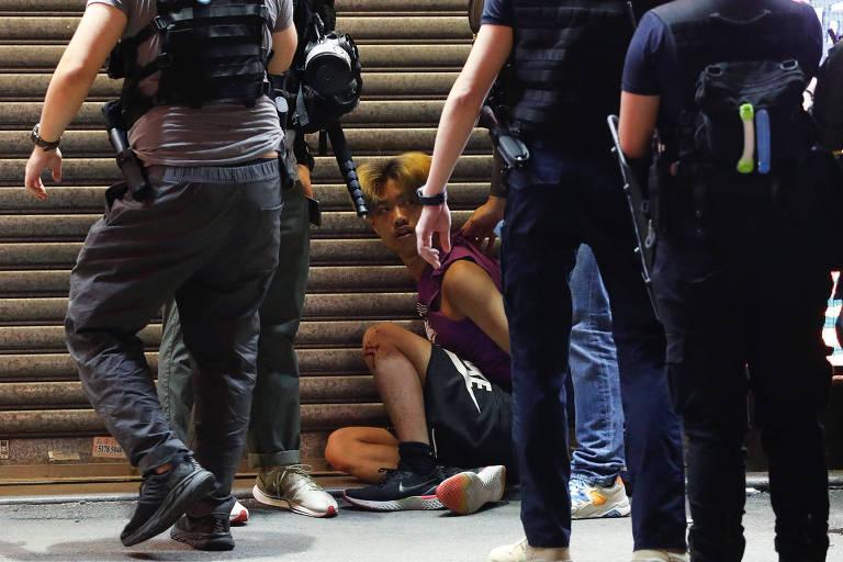 Policiais prendem homem durante protesto contra adiamento das eleições em Hong Kong neste domingo (6)