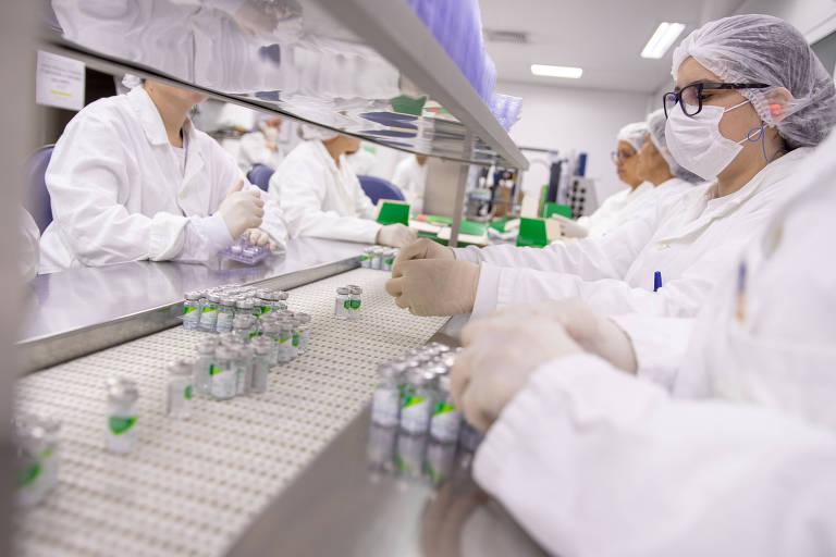 linha de produção de vacinas, com funcionários paramentados manipulando frascos