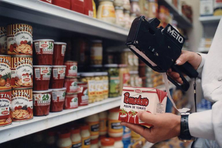 Atendente durante remarcação de preços em produtos de supermercado